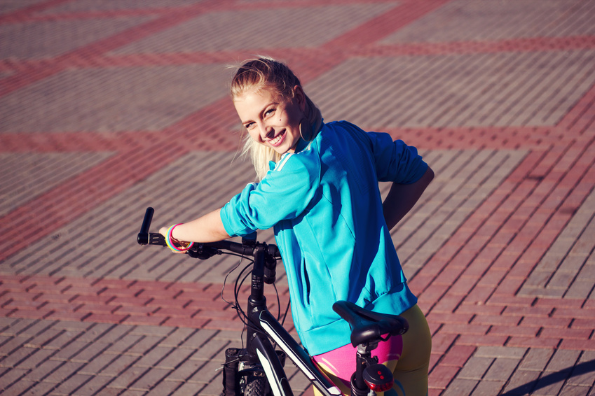 Girl with bicycle smiling and looking in camera